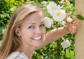 Woman with a beautiful smile and healthy teeth happy on background of flowers Royalty Free Stock Photos