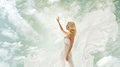 Woman beauty girl in fluttering dress over sky blonde white with flying fabric beautiful showing advertise on Royalty Free Stock Images