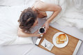 Woman in bed eating breakfast Royalty Free Stock Photo