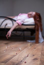 Woman in bed overdose tablet redhead Royalty Free Stock Photography