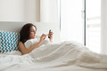 Woman in bed with smartphone Royalty Free Stock Photo