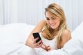 Woman On Bed Using Cellphone