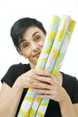 Woman behind gift paper slanting head and shoulder shot of a black haired middle aged yellow green rolls forward holding against Stock Images