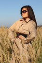 Woman in beige autumn coat and sunglasses posing Stock Images