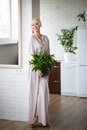 Woman in a beige dress with a bouquet of mint in hand, standing Royalty Free Stock Photo