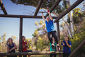 Woman being cheered bye her teammates to climb monkey bars during obstacle course training Royalty Free Stock Photo
