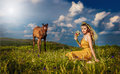Woman belly dancer relaxing on grass field against blue sky with white clouds Royalty Free Stock Photo