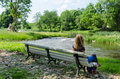 Woman on bench admire fast flow river water stream Royalty Free Stock Photo