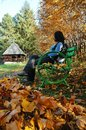 Woman on bench in park at Autumn Stock Photography