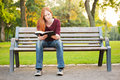 A woman on a bench reading a bible casual young sitting in park and her Stock Image