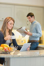 Woman with beverage and tablet computer and man with newspaper men in kitchen Stock Photos
