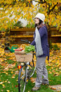 Woman with bicycle a apples and in the garden Stock Image