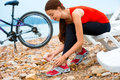 Woman with bicycle on the beach young sport tying laces sunbed near sea background Royalty Free Stock Photos