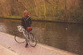 Woman on bicycle by canal a young is her the Stock Photography