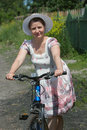 Woman on a bicycle middle aged in hat Royalty Free Stock Photography