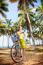 Woman with bicycle in nature and basket on the beach near palm trees and ocean india Royalty Free Stock Photos