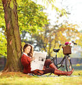 Woman with bicycle sitting on a grass and reading a newspaper in young green park shot tilt shift lens Royalty Free Stock Photo