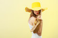 Woman in big yellow summer hat holds sandals Royalty Free Stock Photo