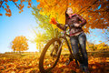 Woman with bike on a autumn leafs background Stock Photo