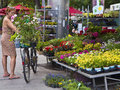 Woman with bike buys flowers at viktualien markt in munich wonam summer frock flower a booth of center Royalty Free Stock Images