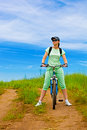 Woman with bike on green field Stock Photos