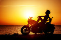 Woman biker enjoying sunset female riding motorcycle motorbike driver traveling the world girl resting on the beach road freedom Royalty Free Stock Photography