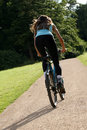 Woman biking on the road Royalty Free Stock Photo