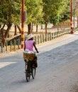 A woman biking on rural road in Bagan, Myanmar Royalty Free Stock Photo