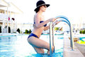 Woman in bikini coming out from swimming pool Royalty Free Stock Photo