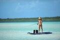 Woman in bikini fishing and paddle boarding Royalty Free Stock Photo