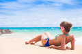 Woman in bikini and flower in hair and sunglasses lying on tropical beach Royalty Free Stock Photo
