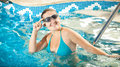 Woman in bikini and goggles smiling at camera at swimming pool young Royalty Free Stock Images