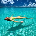 Woman in bikini lying on water at tropical beach Stock Image