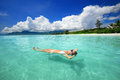 Woman in bikini relaxing lying on the water against background of beach and mountains Royalty Free Stock Image