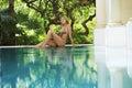 Woman In Bikini Sitting By Swimming Pool Royalty Free Stock Photo