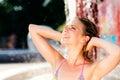 Woman in bikini at the splashing fountain summer heat having fun and water Royalty Free Stock Images