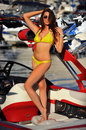 Woman in bikini and sunglasses posing pretty on motor speed boat beautiful brunette during the sunny summer day Stock Image