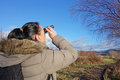 Woman with binoculars birdwatching looking up at tree Stock Photo