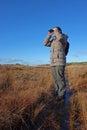 Woman with binoculars birdwatching standing on boardwalk in wetland Royalty Free Stock Images