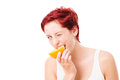 Woman bites in a orange winking on white background Royalty Free Stock Photos