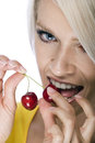 Woman biting a luscious cherry close up of the face of beautiful young blond with look of pleasurable anticipation as she Stock Image