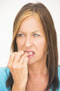 Woman biting nervous finger portrait attractive but and anxious looking mature fingernails with worried and stressed facial Royalty Free Stock Photo