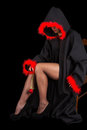 Woman in black cape with red fringe and flower sit Stock Photography