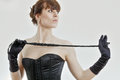 Woman black corset white background holds riding crop Stock Image