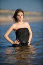 Woman in black dress at the beach getting wet Royalty Free Stock Photo