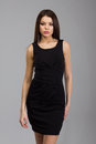 Woman in a black dress beautiful standing over gray background Stock Images