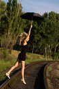 Woman in black dress flying on an umbrella Royalty Free Stock Photo