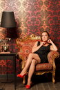 Woman in black dress sitting on vintage chair Royalty Free Stock Image