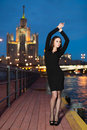 Woman in black dress standing on the waterfront lifted hands young background night city Stock Image
