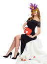 Woman in black evening gown and carnival mask with gift box. Sit on white fur. Valentine holiday and party concept.